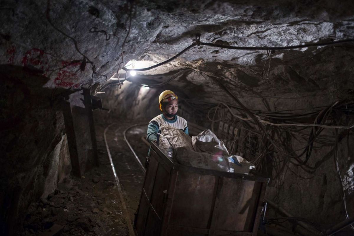 A miner pushes a cart carrying rocks embedded with gemstones inside the Mogok Pride mine in Mogok, Myanmar, on March 14, 2016.