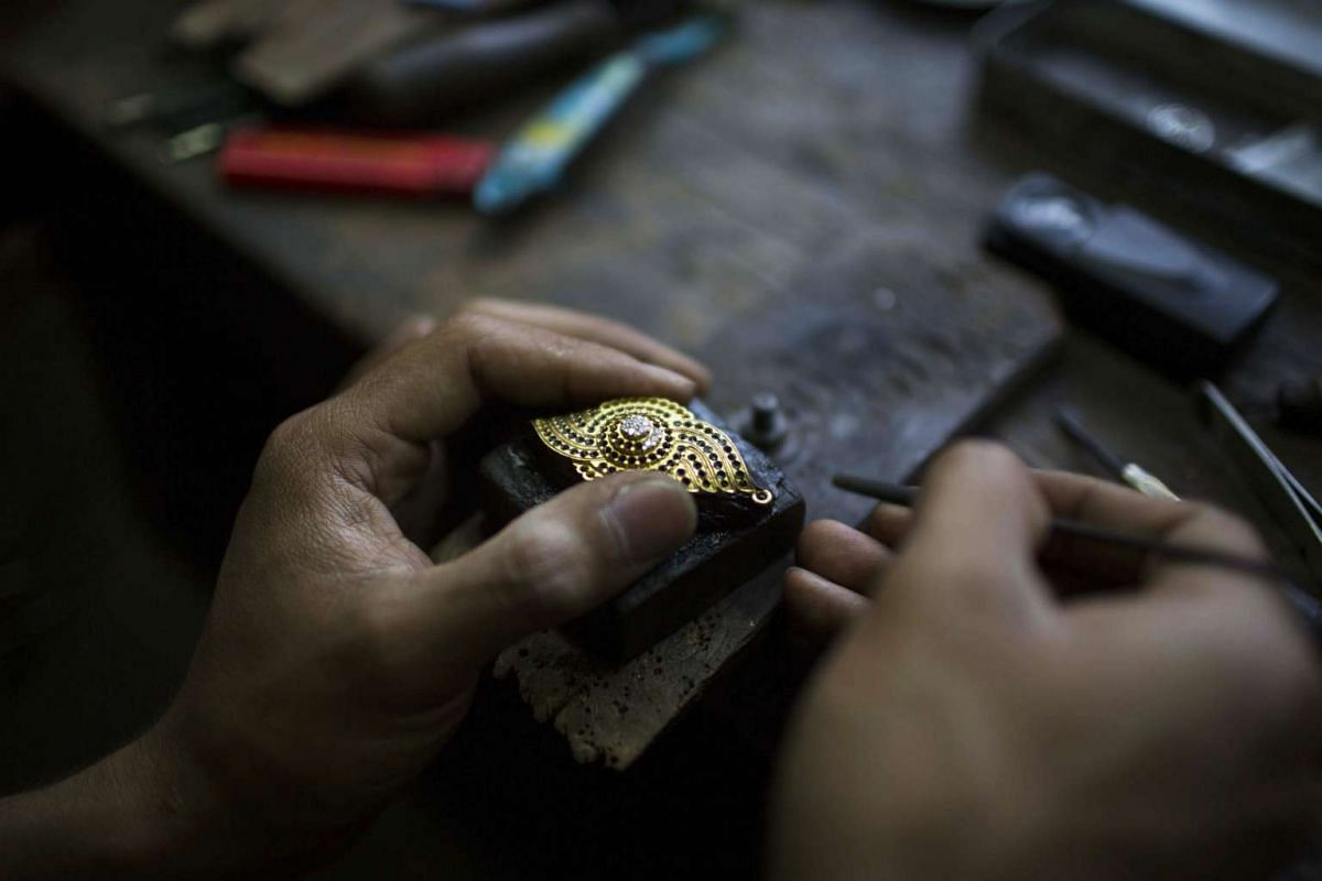 A craftsman inlays gemstones into a piece of gold jewellery at a workshop in Mogok, Myanmar, on March 13, 2016.
