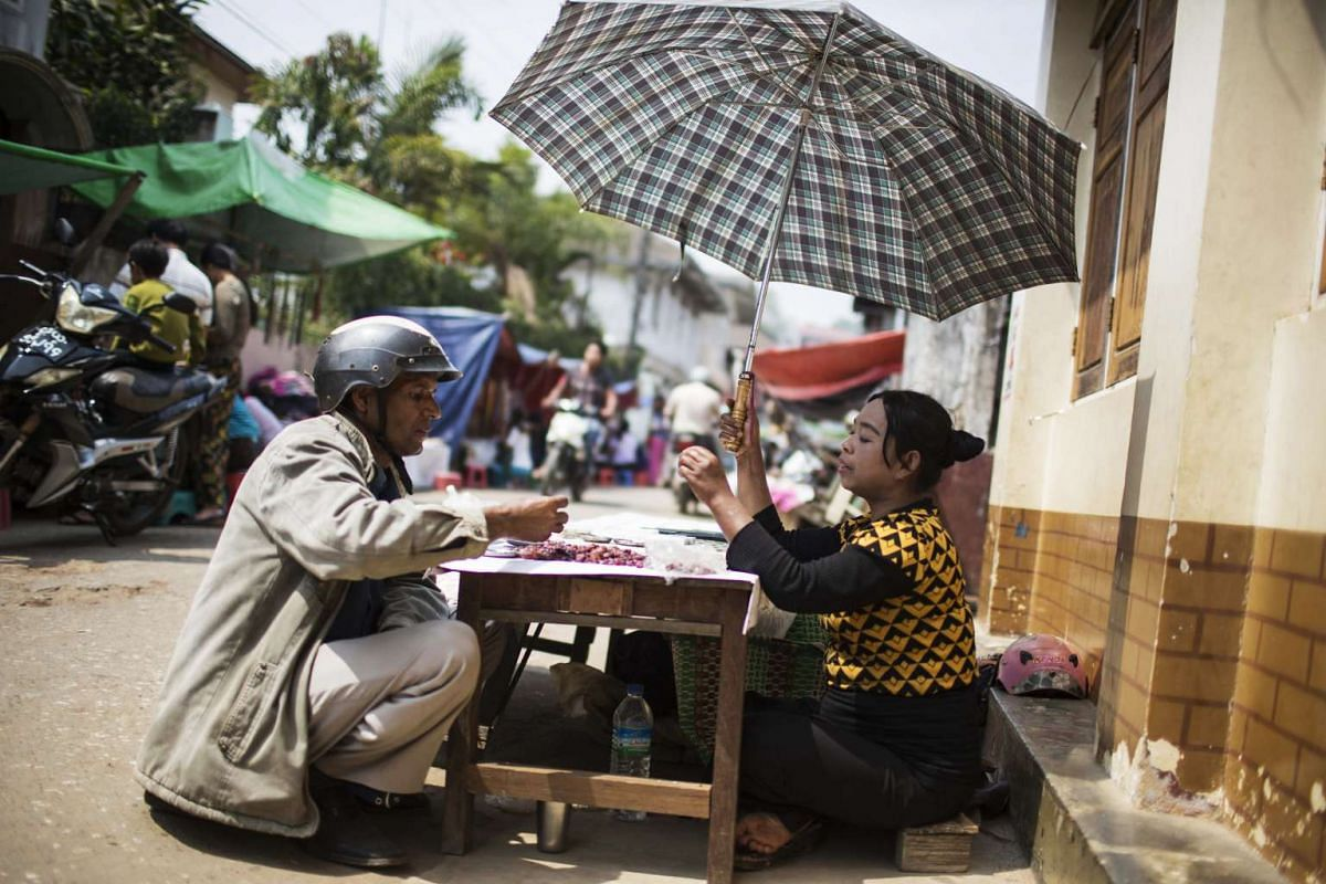 A vendor (right) assists a customer at a gemstone market stall in Mogok, Myanmar, on March 14, 2016.