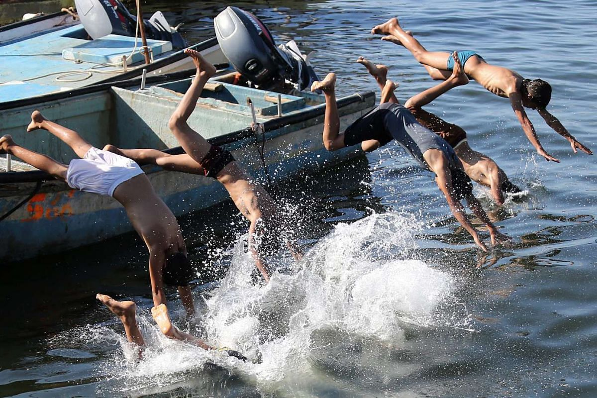 Palestinian boys jumping into the sea in the port of Gaza in hot weather in the Gaza Strip on May 18, 2016.
