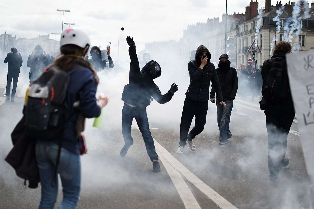 A protester throws a projectile during clashes with riot police to demonstrate against the government's planned labour law reforms in Nantes, western France on May 19, 2016.