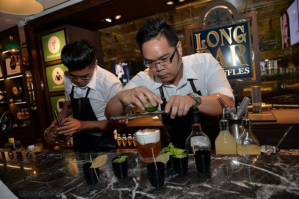 Nathan Soh (far left) and Byron Tan make the Fatty Old Fashioned, an amalgamation of the classic Old Fashioned and nasi lemak.
