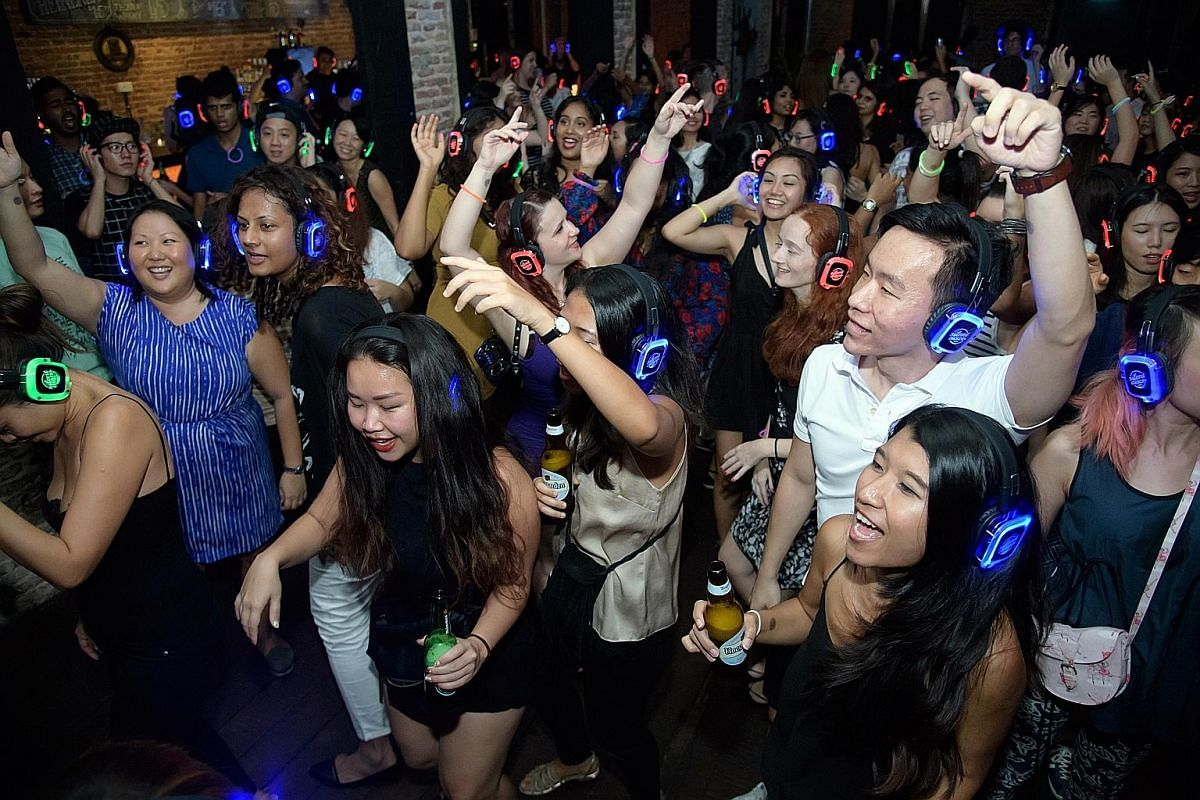 The coloured lights on partygoers' headphones indicate the music station they are listening to.