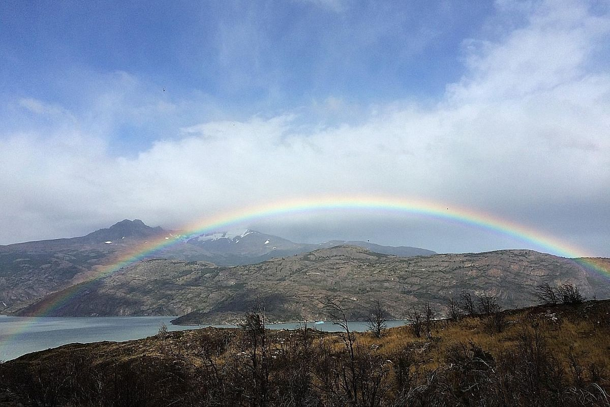 A rare cloud (above left) crafted by powerful winds into a curve in the sky, like a white rainbow. Rainbows (above) often arc across the landscape in Patagonia because of the mix of rain and sun. A Chilean baqueano (left), or cowboy, tending to one o