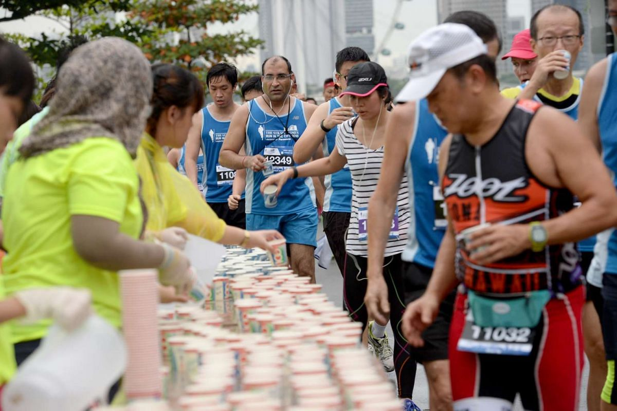 Runners taking a water break in this year's The Straits Times Run, on May 22, 2016.