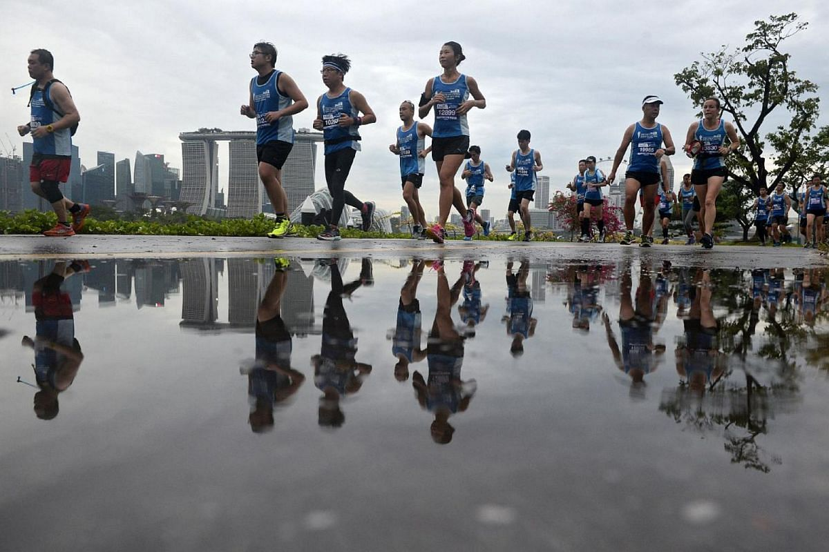 Participants running despite the wet weather during The Straits Times Run 2016.