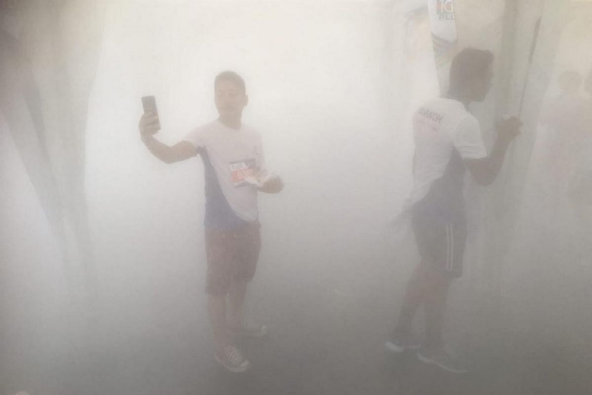 Runners enjoying the mist booth at the carnival area.