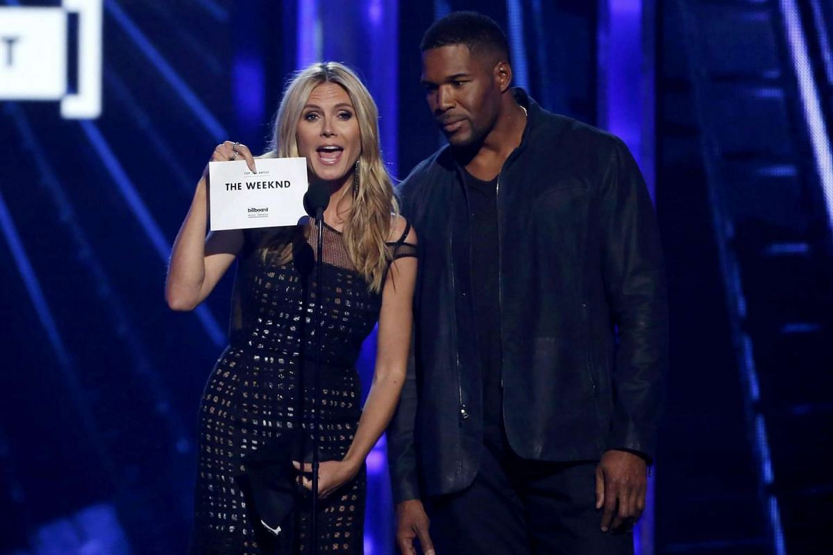 Presenters Heidi Klum (left) and Michael Strahan announce that The Weeknd is the winner for Top Hot 100 Artist at the 2016 Billboard Awards.