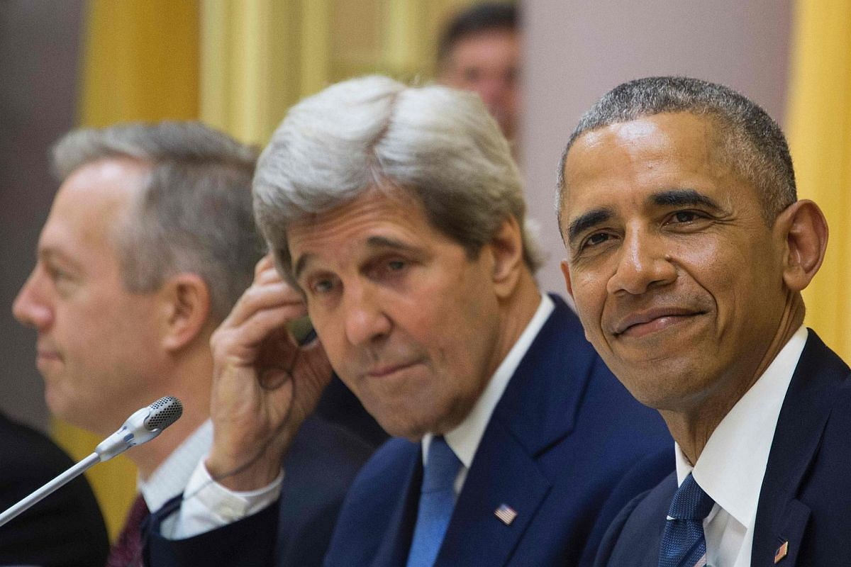 US President Barack Obama (right) and US Secretary of State John Kerry (centre) listening during a bilateral meeting with Vietnamese President Tran Dai Quang (not pictured) at the Presidential Palace in Hanoi on May 23, 2016.