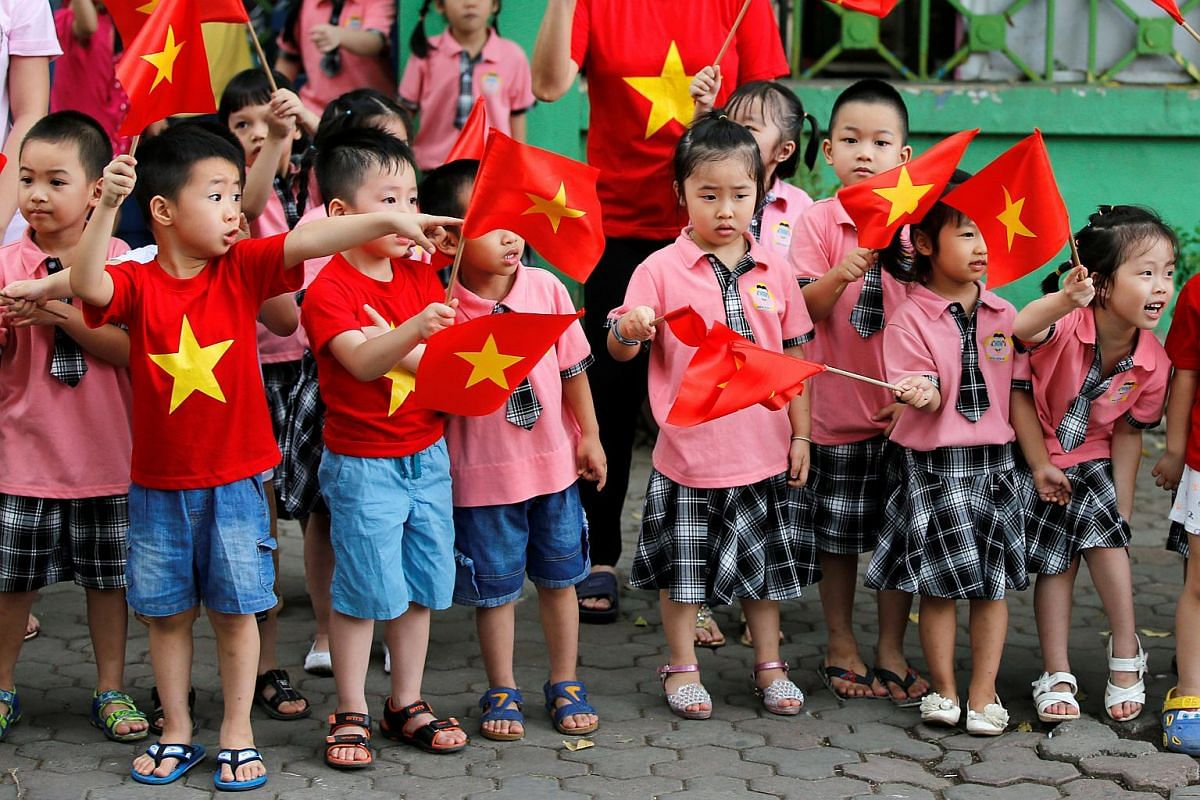 Children look at the motorcade transporting US President Barack Obama before an arrival ceremony at the presidential palace in Hanoi, Vietnam on May 23, 2016.