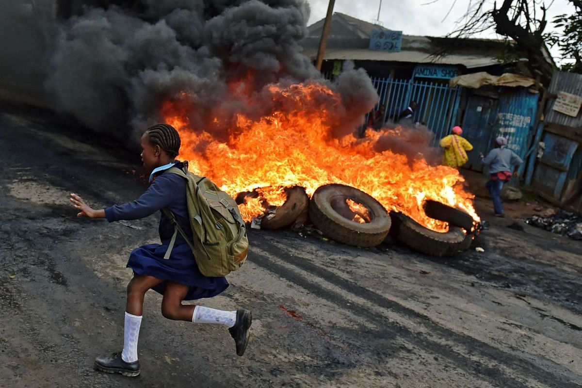 A schoolgirl runs past a burning barricade in Kibera slum, Nairobi, Kenya, on May 23, 2016, during a demonstration of opposition supporters protesting for a change of leadership ahead of a vote due next year. PHOTO: AFP