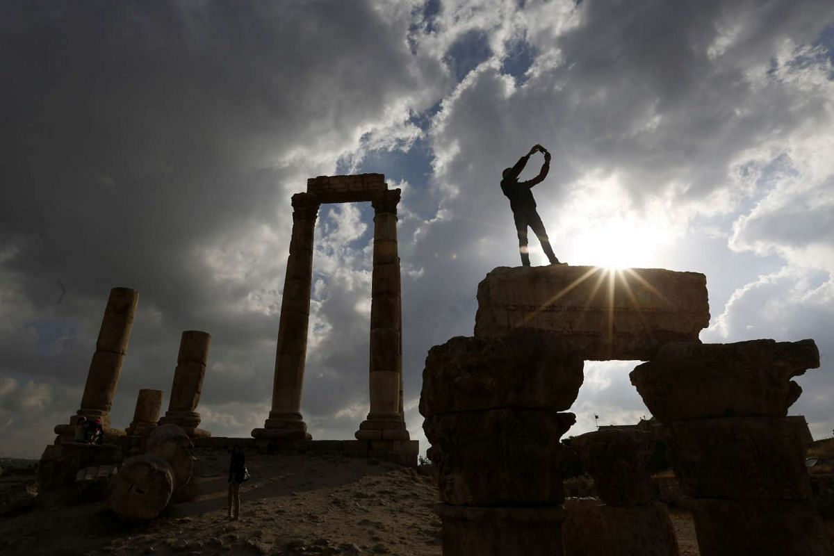 A tourist takes pictures next to the pillars of the Roman Temple of Hercules during his visit to the Amman Citadel, an ancient Roman landmark in Amman, Jordan, May 23, 2016. PHOTO: REUTERS