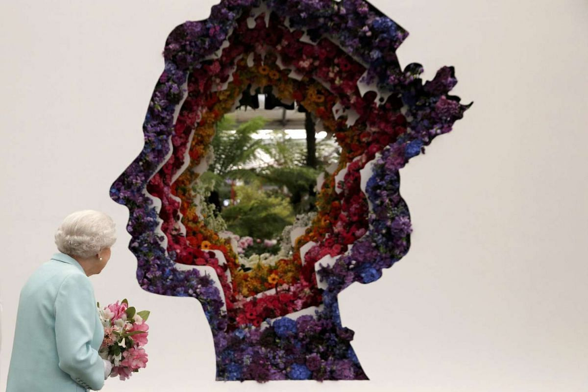 Britain's Queen Elizabeth II stands in front of a floral exhibit by the New Covent Garden Flower Market, which features an image of the Queen at the 2016 Chelsea Flower Show in central London, May 23, 2016. PHOTO: REUTERS