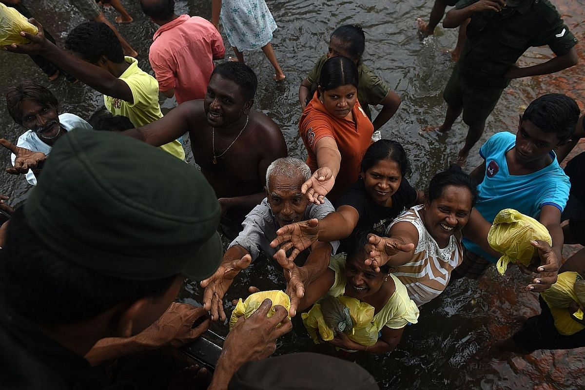 A Sri Lankan man in Kelaniya, on the outskirts of Colombo, examining a piece of furniture swept away by floods on Sunday. At least 92 people have died from massive floods and landslides in Sri Lanka. Villagers in Chittagong, Bangladesh, inspecting wh