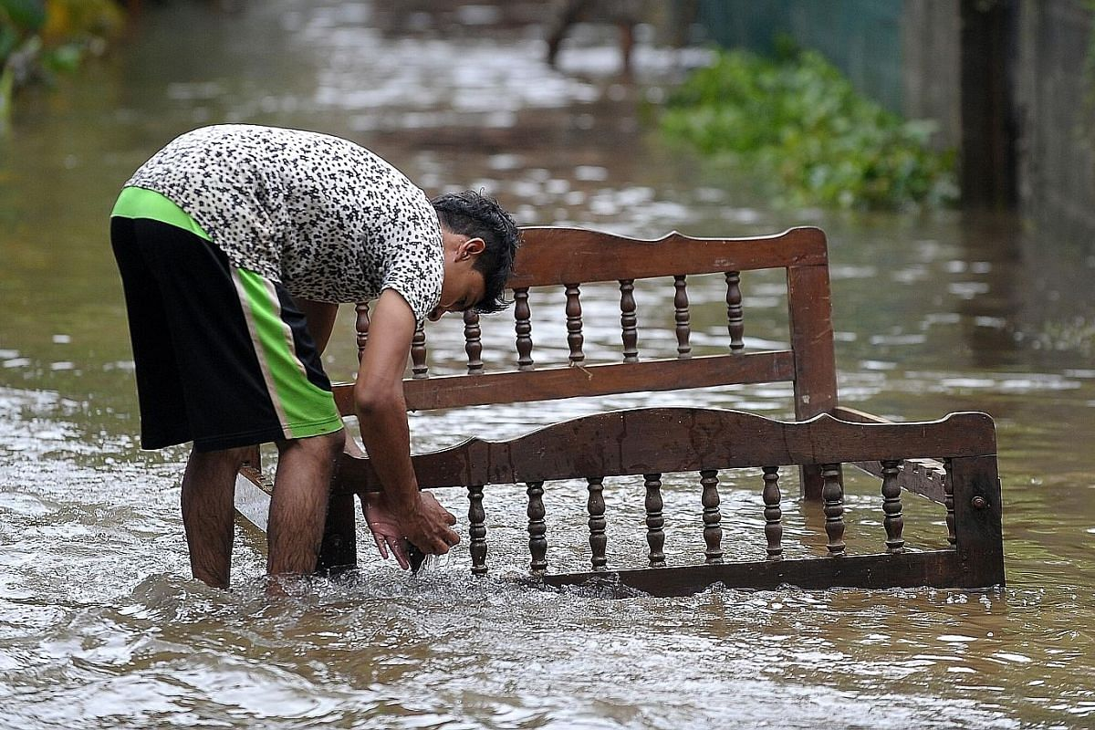 (Centre left) The village of Mujiang, in Guangxi province's Fuchuan Yao Autonomous County, is nearly submerged in floodwaters after torrential rains lashed the region. More than a million people have been affected by the rain.