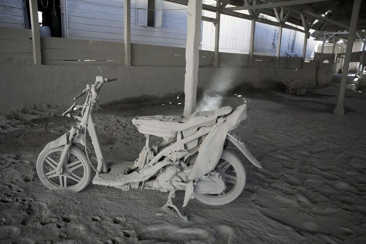 A motorcycle is seen covered in volcanic ash following Mount Sinabung's eruption in Gamber village, Indonesia, on May 23, 2016.