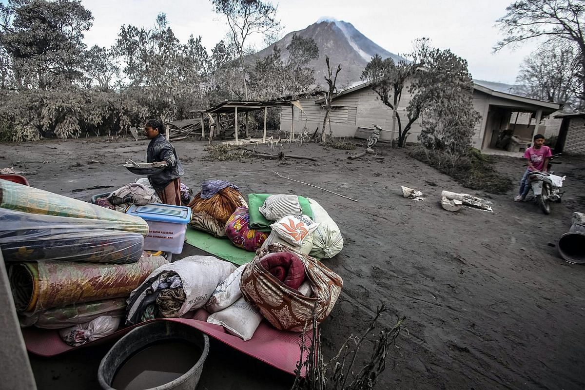 Residents gather their belongings as they evacuate from a village impacted by the Mount Sinabung eruption at Gamber Village, Indonesia, on May 22, 2016.