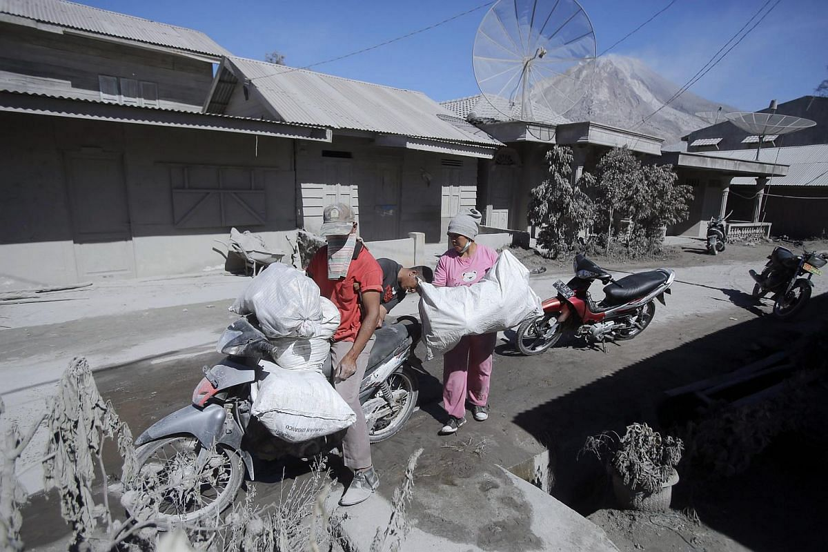 Indonesian villagers collect their belongings as they evacuate from a village hit by Mount Sinabung's eruption, in Gamber Village, Indonesia, on May 23, 2016.