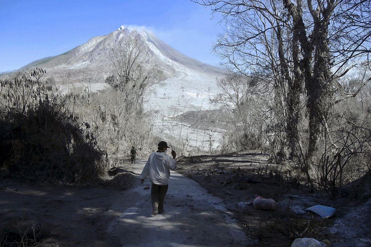 Indonesian soldiers inspect an empty village hit by Mount Sinabung's eruption, in Gamber Village, Indonesia, on May 23, 2016.