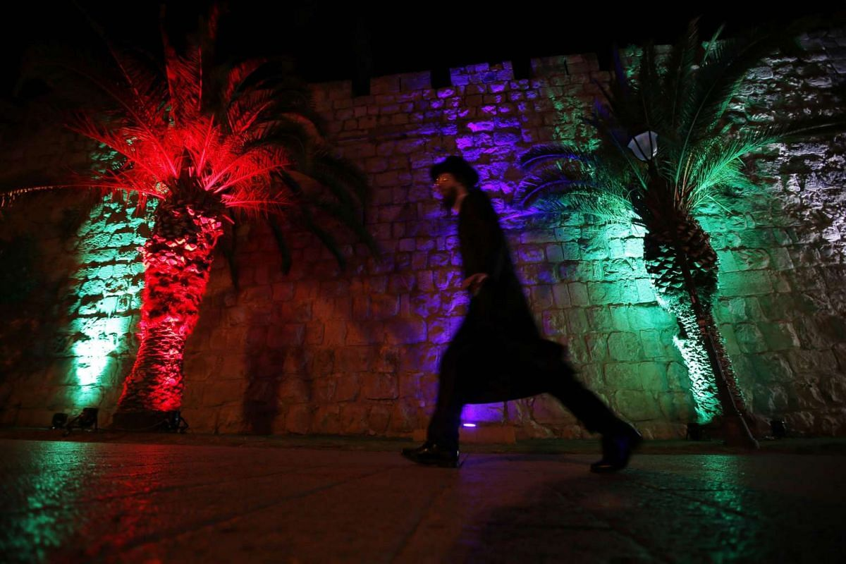 A man walks past an illuminated colors light show projected on the ancient walls of Jerusalem's Old City during the Jerusalem Festival of Lights on May 24, 2016. PHOTO: AFP