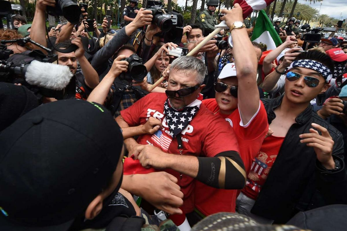 Anti-Trump protesters (L) clash with Donald Trump supporters (C) outside the Anaheim Convention Centre during a rally for Republican presidential candidate Donald Trump on May 25, 2016, in Anaheim, California. PHOTO: AFP