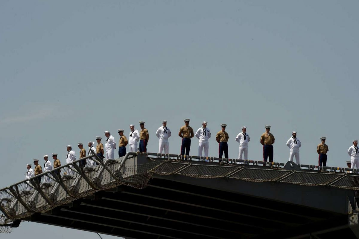 """Sailors and marines stand on the deck of the USS Bataan (LHD 5) as it arrives into Pier 88 during the """"Parade of Ships"""" ceremony to kick off Fleet Week in New York on May 25, 2016. PHOTO: AFP"""