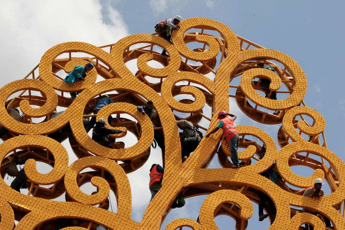 Workers fixer a metal tree installed in the city of Managua by the government to decorate the Nicaraguan capital, May 25,2016. PHOTO: REUTERS