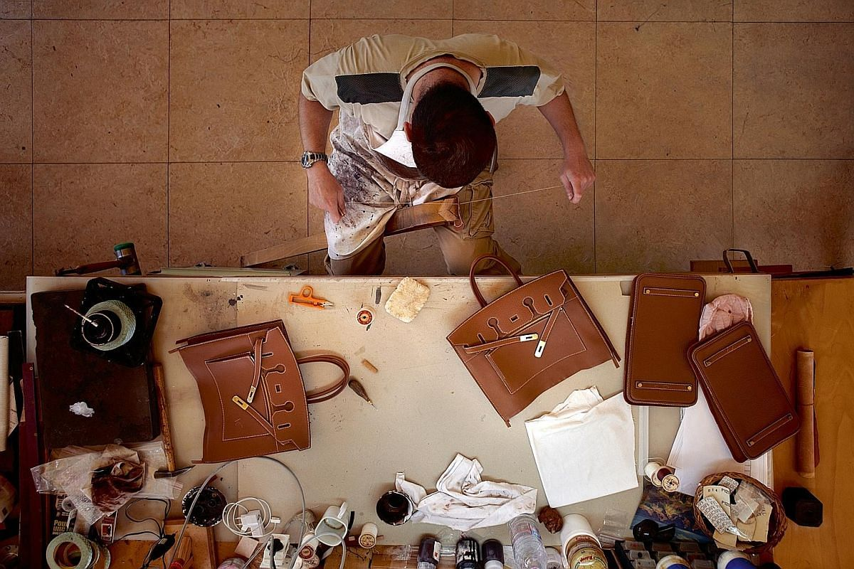 Hermes' womenswear (left) and the brand's newly renovated flagship store at Liat Towers (right). It takes about two years to train an Hermes craftsman, with each one supervised by an existing craftsman.
