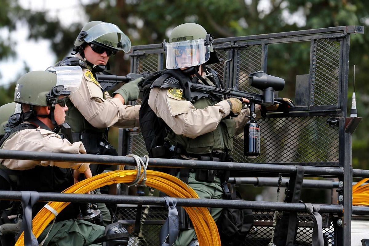 Los Angeles Sheriff Department deputies stand with non-lethal weapons behind a truck mounted barrier to disperse demonstrators after US Republican presidential candidate Donald Trump spoke at a campaign event in Anaheim, California, US on May 25, 201