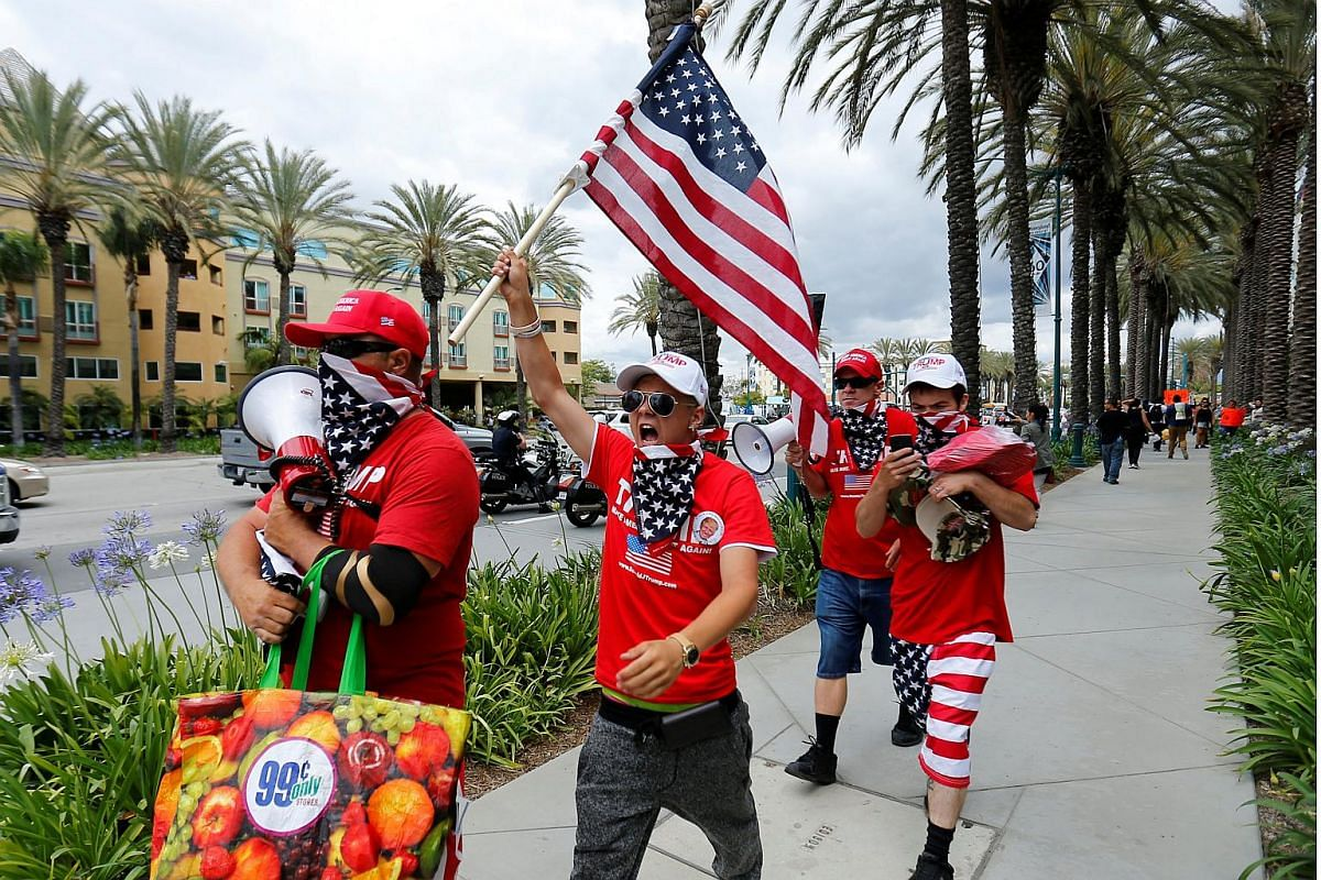Supporters of US Republican presidential candidate Donald Trump march down a street waving the US flag after Trump spoke at a campaign event in Anaheim, California, US on  May 25, 2016.