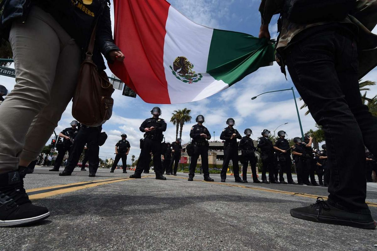 Protestors unfurl the Mexian flag before police outside the Anaheim Convention Center prior to a rally for the US Republican presidential candidate Donald Trump on May 25, 2016 in Anaheim, California.