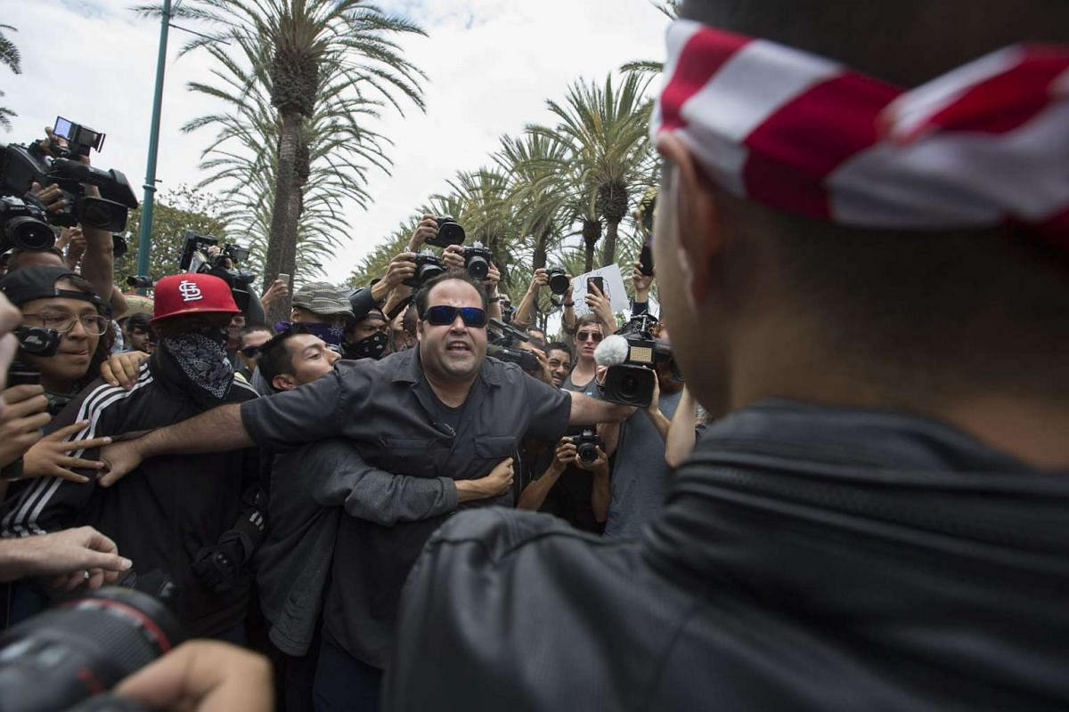 An anti-Trump protester (left) and a Trump support clash outside a campaign rally by US Republican presidential candidate Donald Trump at the Anaheim Convention Center on May 25, 2016 in Anaheim, California. Previous visits by the candidate to Orange