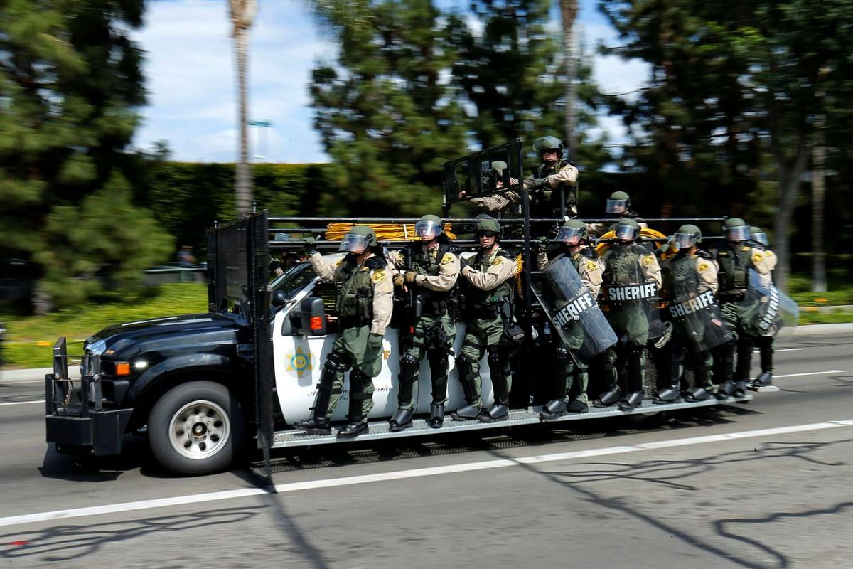 Los Angeles County Sheriffs in riot gear speed down a road as they chase demonstrators protest near the convention center where US Republican presidential candidate Donald Trump held a campaign rally in Anaheim, California, United States May 25, 2016