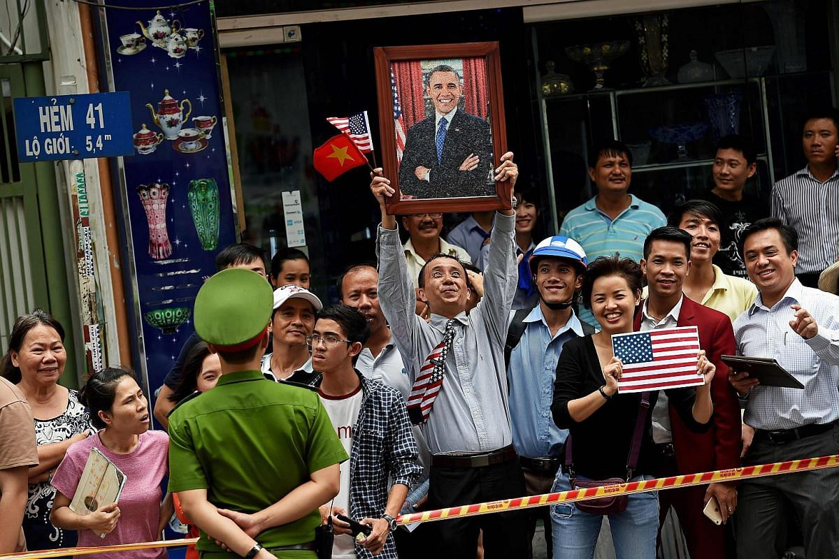 A man holding a portrait of US President Barack Obama as people line the streets to catch a glimpse of the US leader on his way to the airport at the end of his visit to Ho Chi Minh City on May 25.