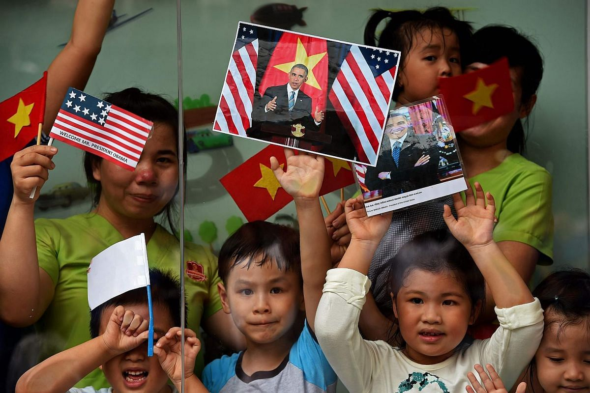 Women and children holding Vietnamese and US flags and pictures of US President Barack Obama as people line the streets to catch a glimpse of the US leader on his way to the airport at the end of his visit on May 25.