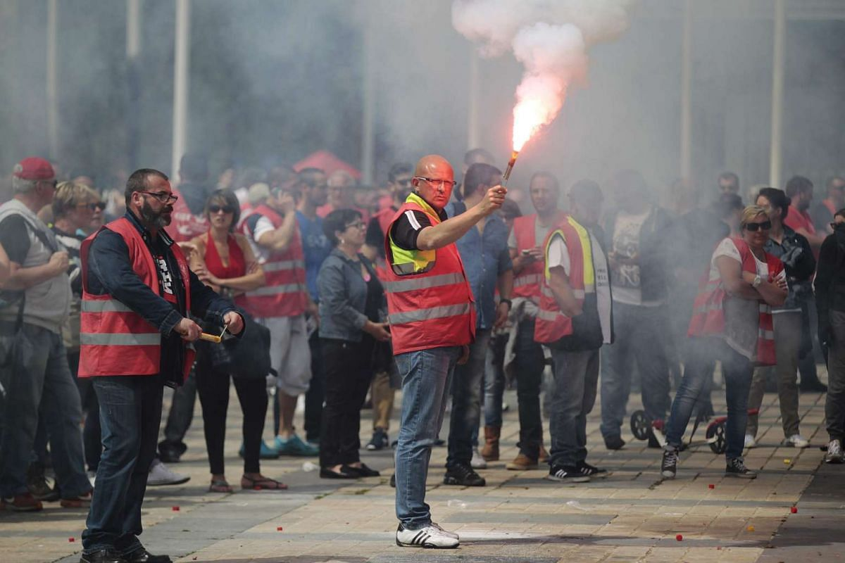 A man holds a flare as people demonstrate in Le Havre northwestern France, on May 26, 2016 to protest against the government's proposed labour reforms. PHOTO: AFP