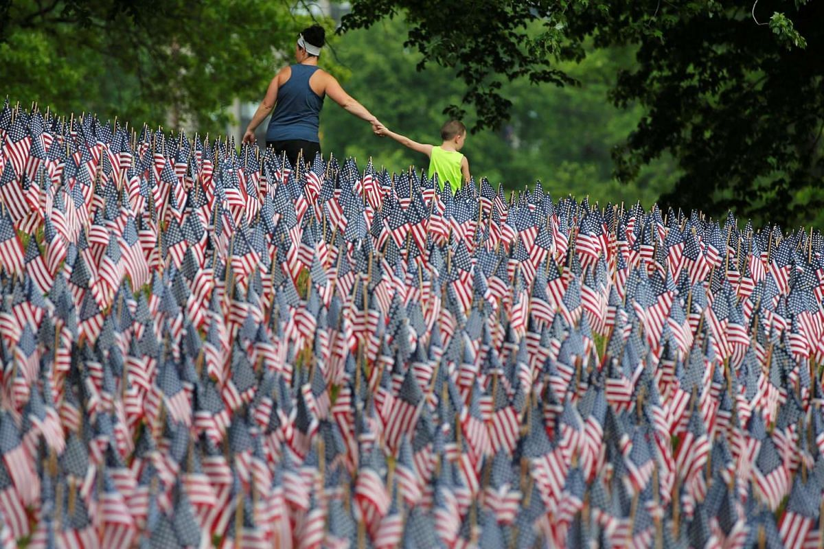 Visitors walk past a field of United States flags displayed by the Massachusetts Military Heroes Fund on the Boston Common in Boston, Massachusetts, U.S. May 26, 2016 ahead of the Memorial Day holiday on May 30.  PHOTO: REUTERS
