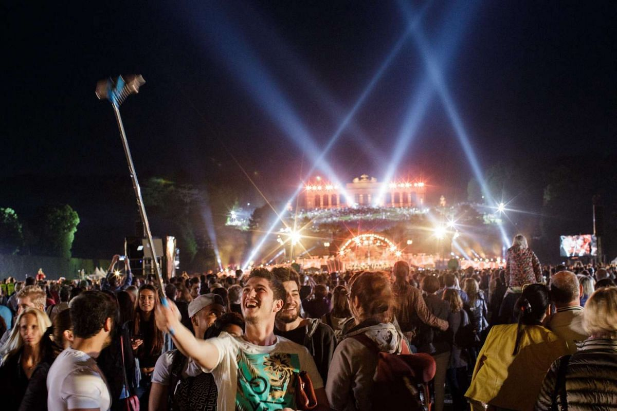 A concert-goer takes a selfie in front of the 'Gloriette' which is seen above a stage set up in the gardens of Schoenbrunn Palace as the Vienna Philharmonic Orchestra performs the 'Summer Night Concert' in Vienna, Austria, May 26, 2016. PHOTO: EPA