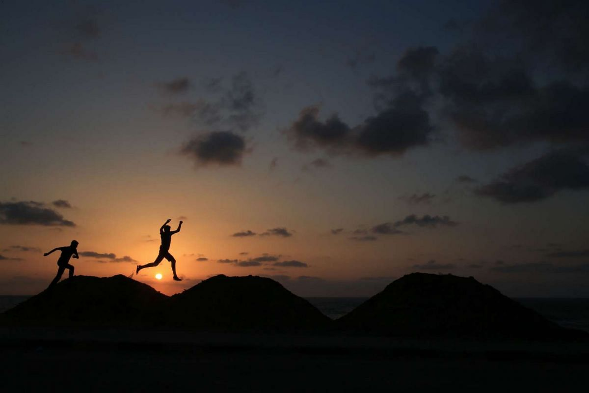Palestinian boys jump along the top of sand dunes as the sun sets in Gaza City on May 26, 2016. PHOTO: AFP