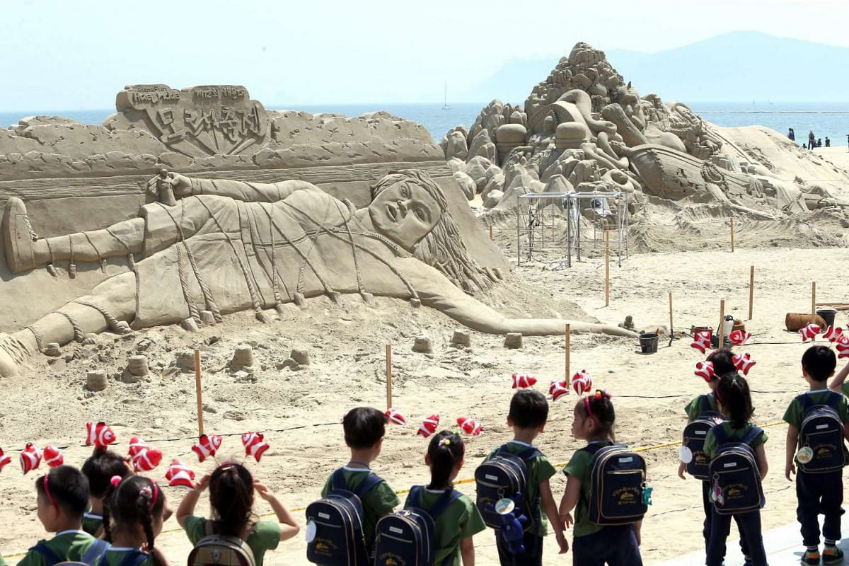Preschoolers look at a sand sculpture depicting a scene from the fairy tale 'Gulliver's Travels' on Haeundae Beach in the southeastern city of Busan, South Korea, May 27, 2016, at an exhibition that opened as part of a four-day sand festival. PHOTO: