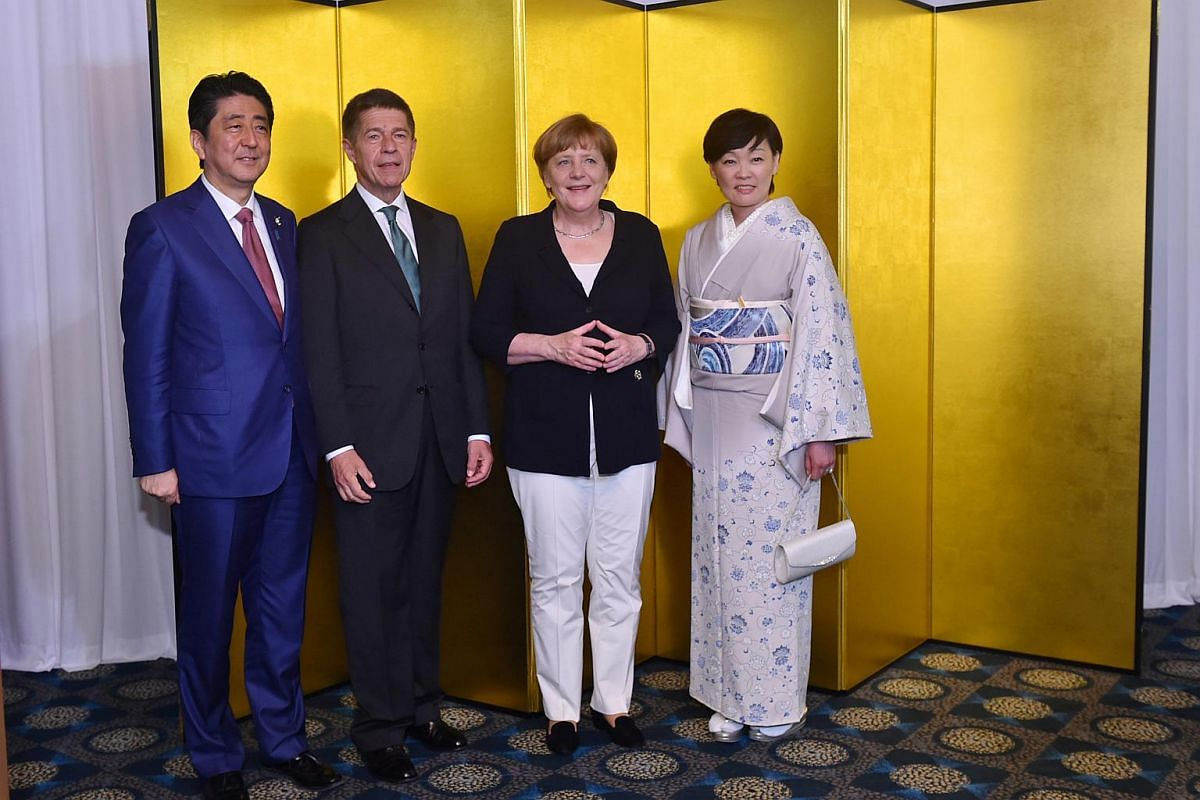 German Chancellor Angela Merkel (second from right) and her husband Joachim Sauer (second from left) with Japanese Prime Minister Shinzo Abe (left) and his wife Akie (right) during the cocktail reception at the Shima Kanko Hotel in Shima, Mie Prefect