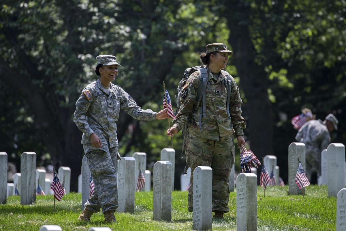 Soldiers from the 3rd US Infantry Regiment, The Old Guard, place American flags in front of headstones during the Flags In ceremony for Memorial Day, at Arlington National Cemetery in Arlington, Virginia, US, May 26, 2016.