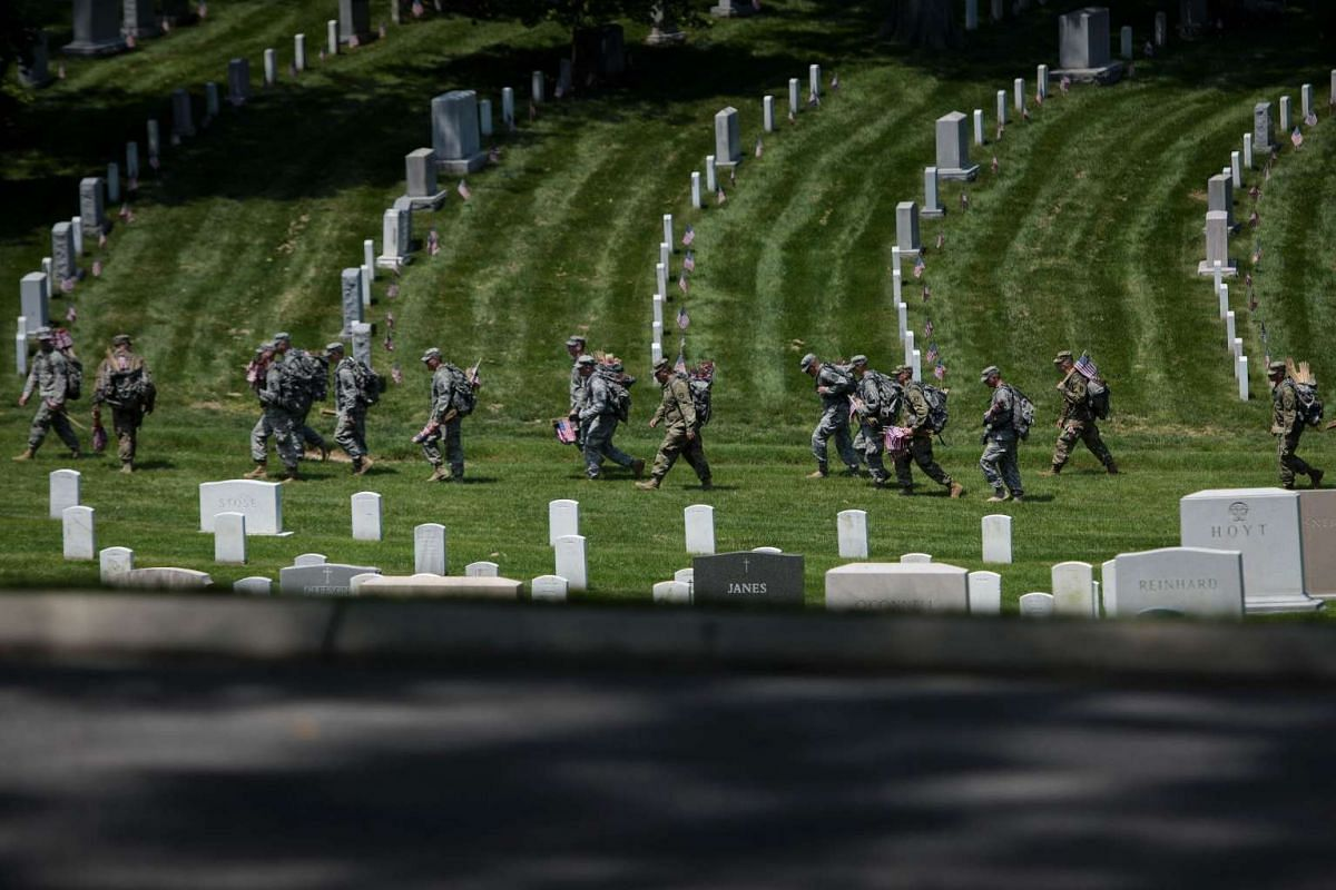 Members of the US Army on their way to place American flags at graves in Arlington National Cemetery on May 26, 2016, in Arlington, Virginia, in preparation for Memorial Day.