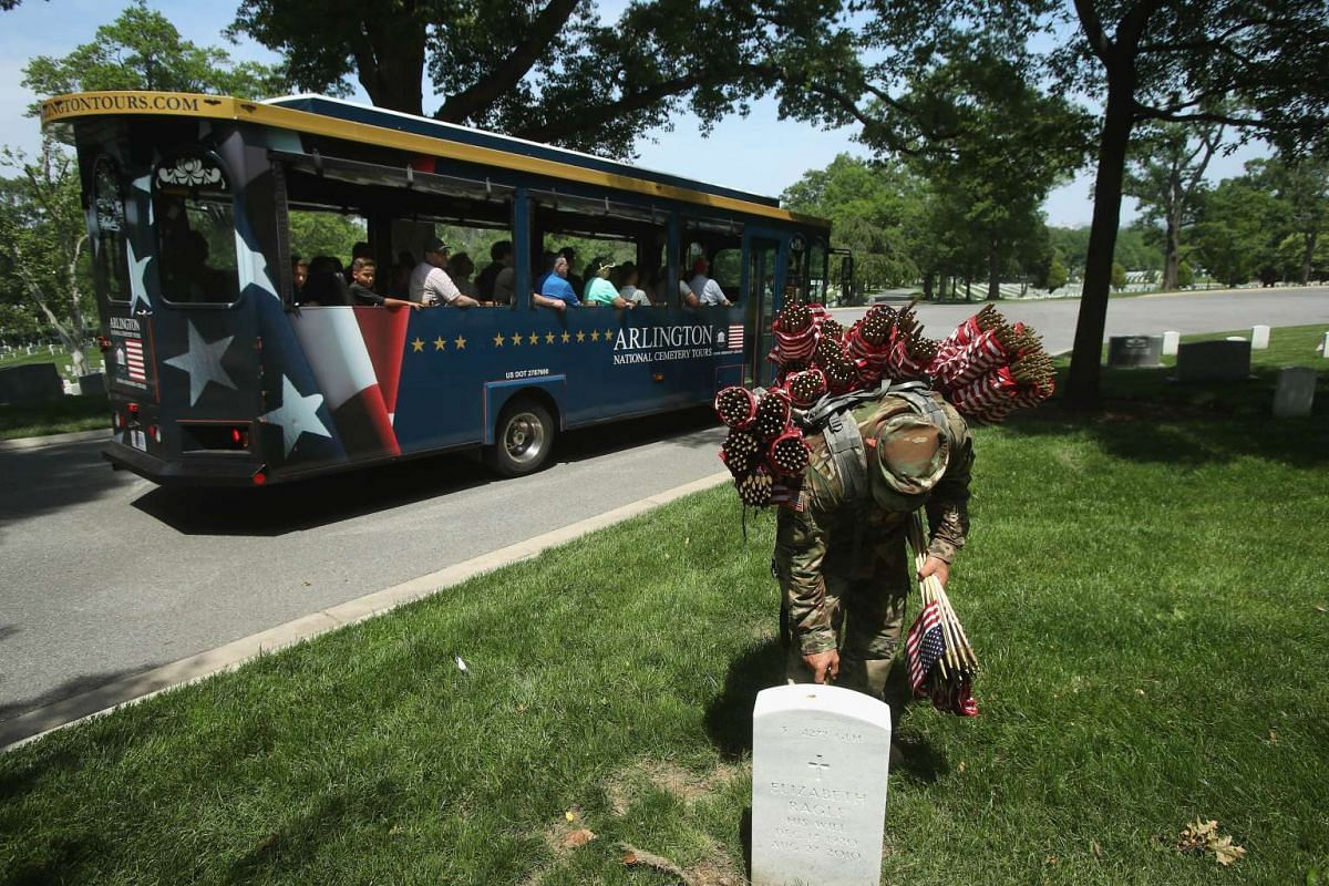 A tour bus passes by as Specialist Jose Barreiro, of the 3rd US Infantry Regiment, The Old Guard, places a flag at a grave site during the Flags In ceremony May 26, 2016, at Arlington National Cemetery in Arlington, Virginia.