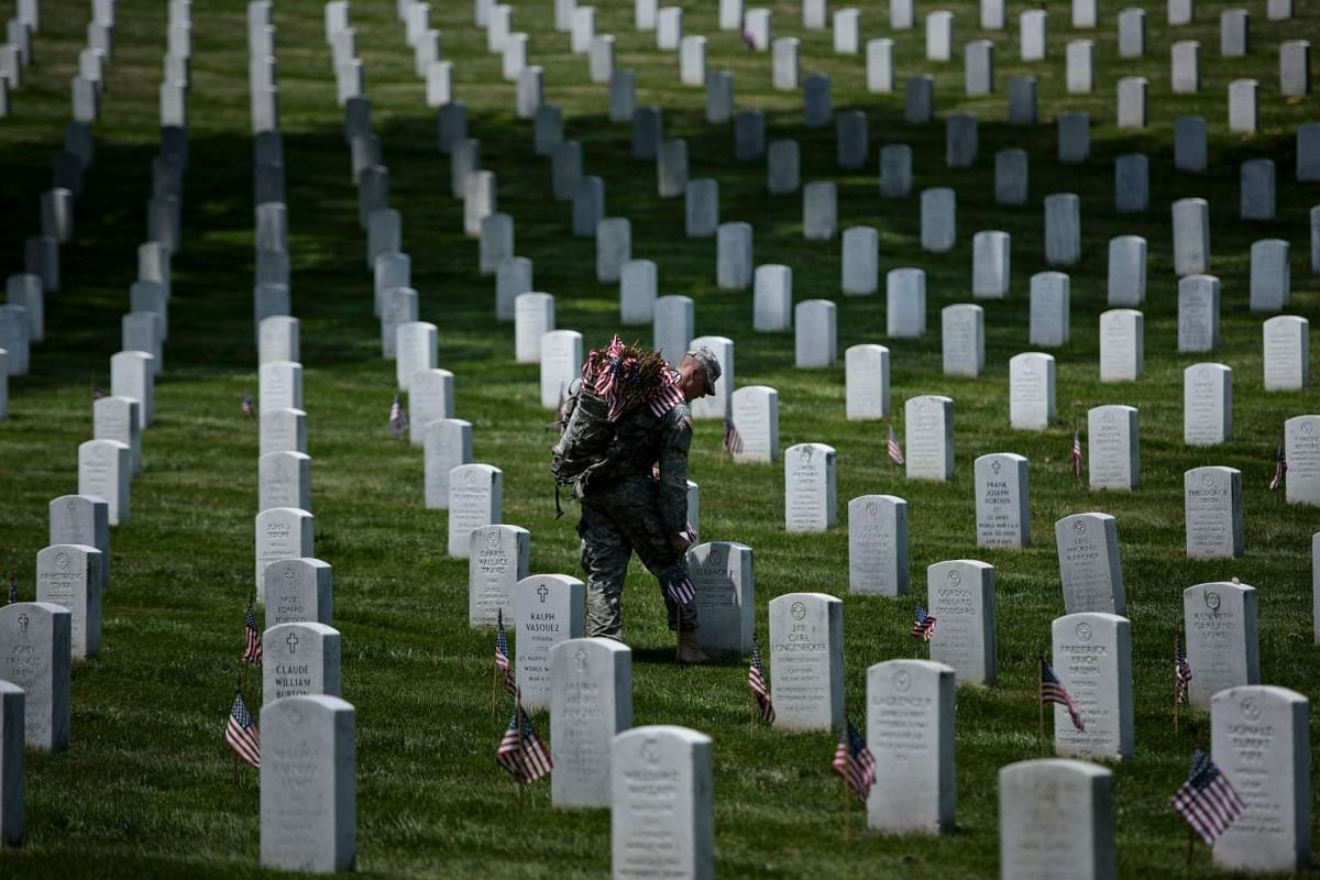 A soldier places American flags at graves in Arlington National Cemetery on May 26, 2016, in Arlington, Virginia, in preparation for Memorial Day.