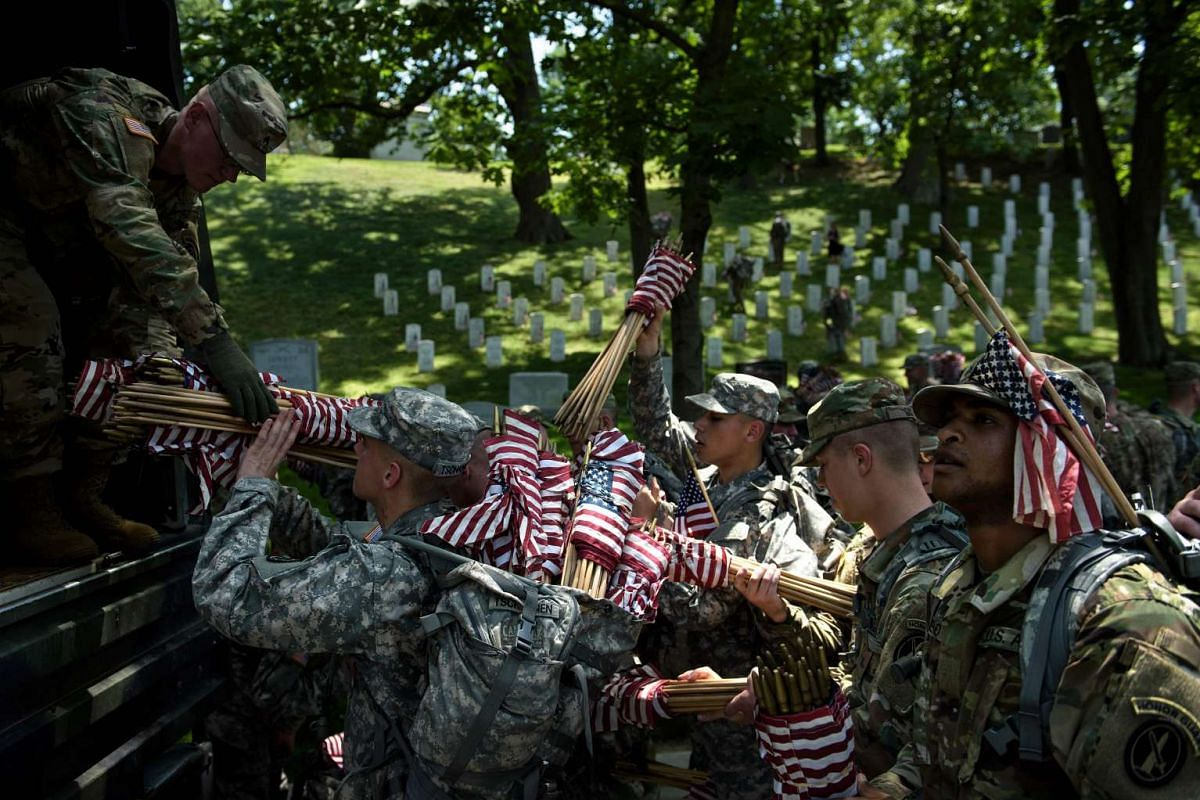 Members of the US Army stock up on American flags before placing them at graves in Arlington National Cemetery on May 26, 2016, in Arlington, Virginia, in preparation for Memorial Day.
