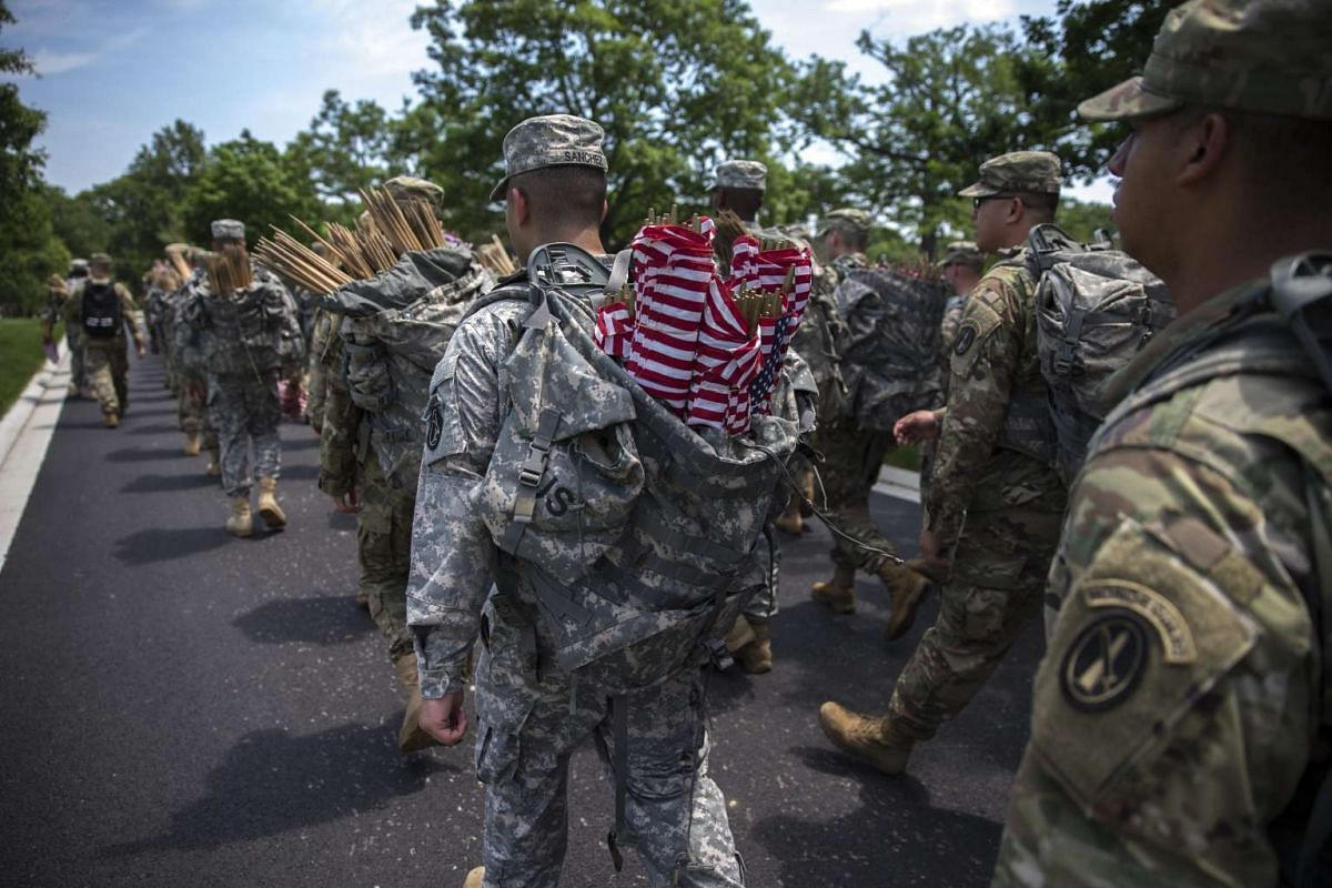 Soldiers from the 3rd US Infantry Regiment, The Old Guard, march with American flags to be placed at every headstone during the Flags In ceremony for Memorial Day, at Arlington National Cemetery in Arlington, Virginia, US, May 26, 2016.