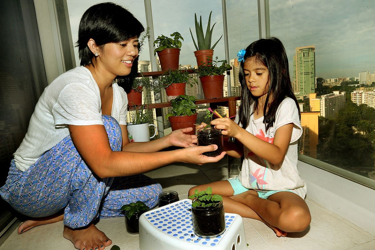 Housewife Samantha Ching-Uy tending her small herb garden with her daughter Alessa.