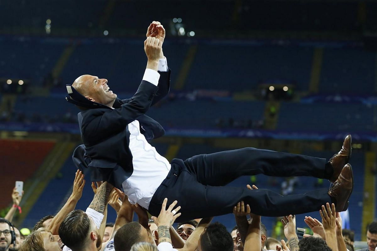 Real Madrid players hoist Zinedine Zidane in the air as they celebrate winning the Uefa Champions League.