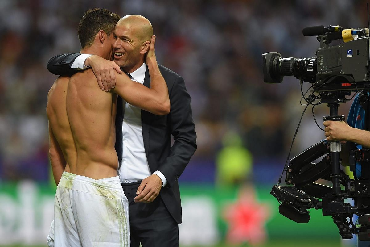 Cristiano Ronaldo (left) celebrates with his coach Zinedine Zidane.